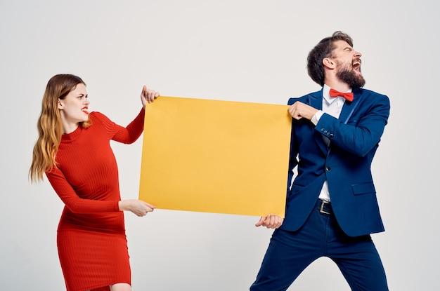 Мужчина в костюме рядом с женщиной в красном платье рекламный плакат желтого макета