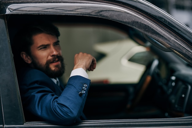 車の窓ガラスの旅の交通機関から覗くスーツを着た男