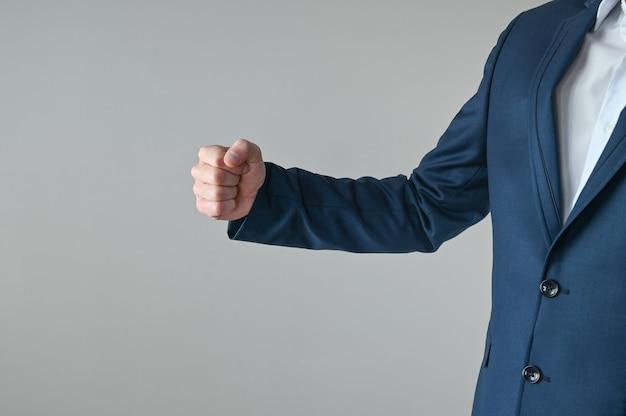 양복 입은 남자가 주먹을 보여줍니다.