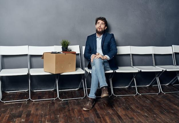 양복 입은 남자가 상자 구직 우울증으로 의자에 앉아있다.