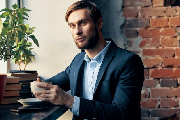 Мужчина в костюме сидит в кафе с чашкой кофе на досуге