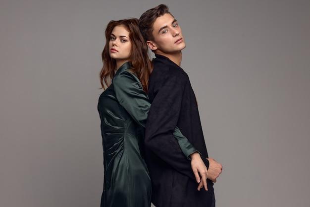 スーツを着た男性が灰色の背景にドレスを着た女性に背を向けて立って手を握る