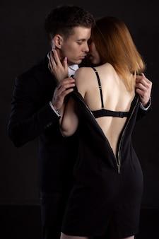 スーツを着た男が情熱的な抱擁の最中に彼のお気に入りの女の子の服を脱ぐ