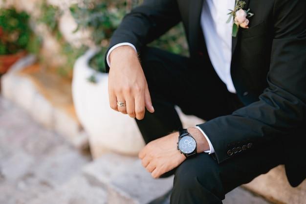 На ступеньке сидит мужчина в костюме с бутоньеркой и наручными часами