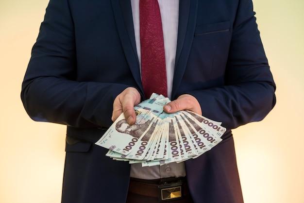 ウクライナのお金の巨大な山とスーツを着た男