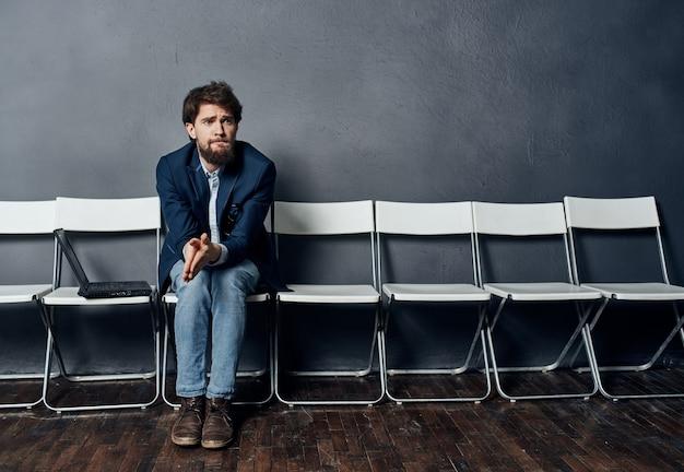 노트북과 양복을 입은 남자가 면접을 기다리는 의자에 앉아 있습니다.