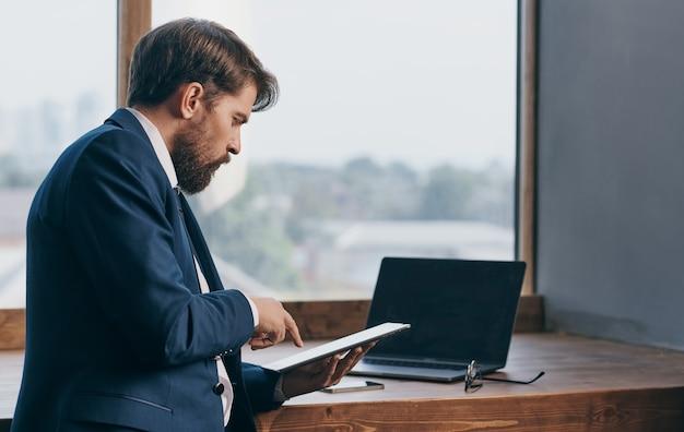 Мужчина в костюме с планшетом в руках офисного чиновника, профессионального бизнесмена.