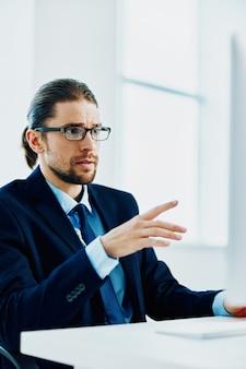 彼の机でタイピング眼鏡をかけたスーツを着た男