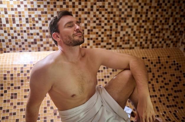 사우나에 앉아 해독 세션을 갖는 수건을 입은 남자