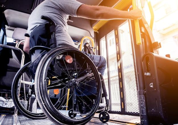 Мужчина в инвалидном кресле в специализированном автомобиле с подъемником для людей с ограниченными возможностями.