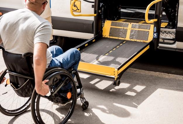 Мужчина в инвалидном кресле движется к подъемнику специализированного автомобиля для людей с ограниченными возможностями.