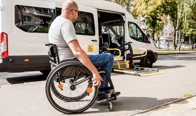 Мужчина в инвалидной коляске движется к подъемнику специализированного автомобиля для людей с ограниченными возможностями.
