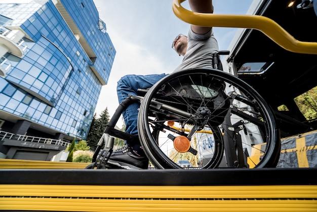 Мужчина в инвалидной коляске на подъемнике специализированного автомобиля для людей с ограниченными возможностями.
