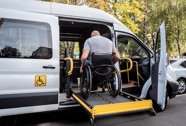 장애인을위한 특수 차량의 리프트에 휠체어를 탄 남자.