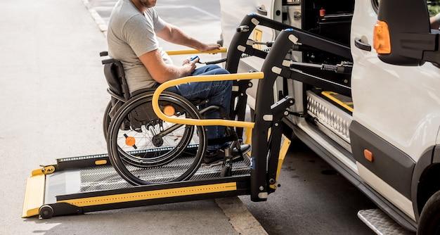 Мужчина в инвалидной коляске на подъемнике автомобиля для людей с ограниченными возможностями.