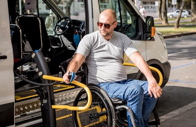장애인을 위해 차량 리프트에 휠체어에 탄 남자.