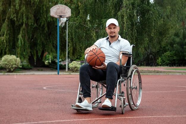 車椅子の男性が運動場でバスケットボールをします。障害者、充実した生活、障害者、フィットネス、活動、陽気さの概念。