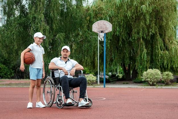 車椅子の男性がスポーツグラウンドで息子とバスケットボールをします。障害者の親、幸せな子供時代、障害者の概念。