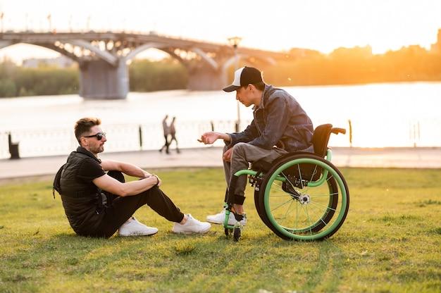 車椅子の男性が公園で車椅子の障害者の友人と一緒に歩いている彼の友人の男性と一緒に歩く