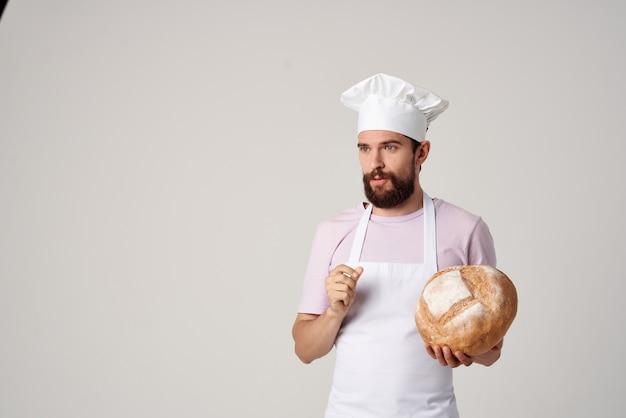 손에 빵을 들고 음식을 요리하는 흰색 앞치마를 입은 남자