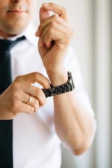 Мужчина в белой рубашке и галстуке надевает часы на руку во время подготовки к свадьбе.