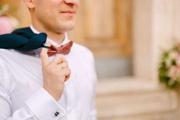 Мужчина в белой рубашке и с красным галстуком-бабочкой держит перекинутую через плечо куртку