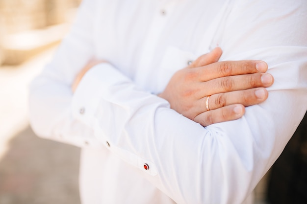 Мужчина в белой рубашке скрестил руки на груди