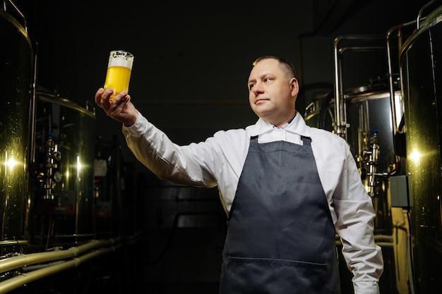 白いシャツを着た男がビールを一杯高く持っている