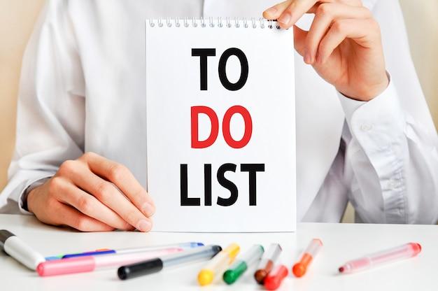 Мужчина в белой рубашке держит листок с текстом: порекомендуйте друга. разноцветные маркеры и планшет на столе. бизнес и образовательная концепция