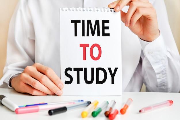 흰 셔츠를 입은 남자가 공부할 시간이 적힌 종이를 들고있다. 프리미엄 사진