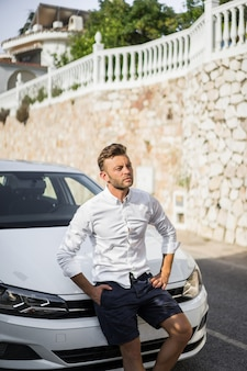 A man in a white shirt is sitting on the hood of a car.