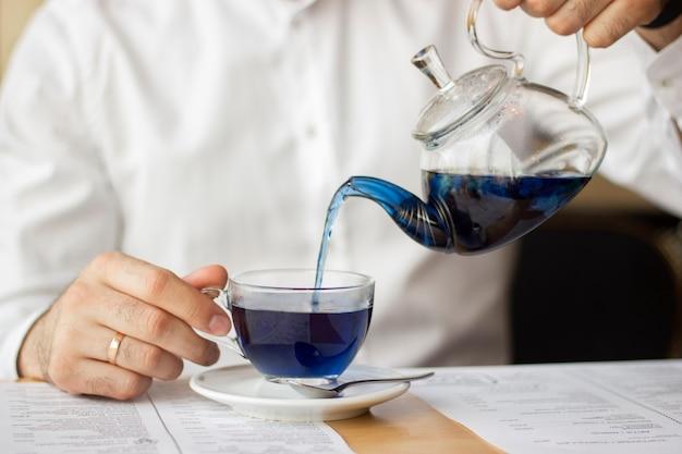 白いシャツを着た男が透明なティーポットからマグカップに青い中国茶を注ぐ
