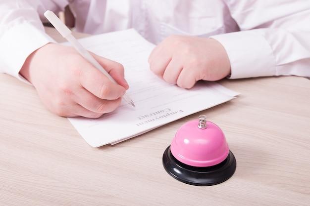 흰 셔츠를 입은 남자가 테이블에 앉아 고용 계약에 서명합니다.