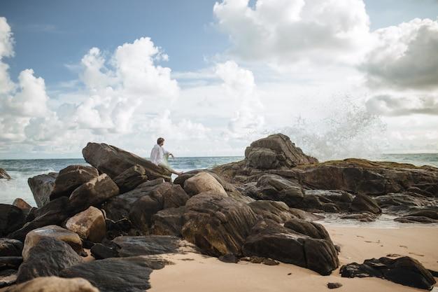 白いシャツを着た男が海の近くの石の上に座っています