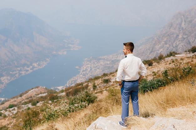Мужчина в белой рубашке стоит на горе ловчен и смотрит на которский залив сзади
