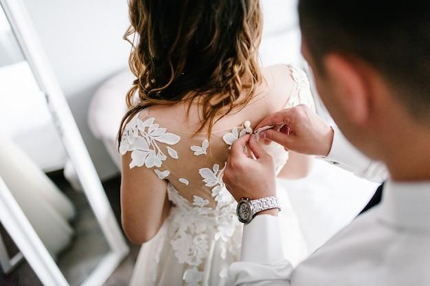 넥타이와 시계가 달린 흰색 셔츠를 입은 남자가 드레스의 코르셋 단추를 잠급니다. 레이스가 집에 서 있는 웨딩 드레스를 입은 신부.