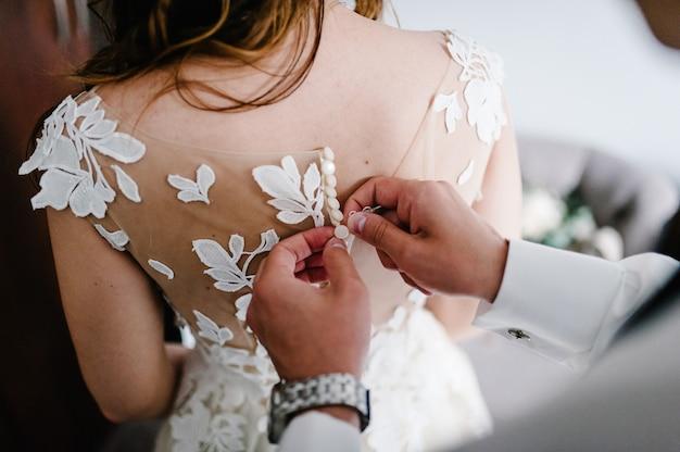넥타이와 시계가 달린 흰색 셔츠를 입은 남자가 드레스의 코르셋 단추를 잠급니다. 방에 서 있는 레이스와 웨딩 드레스의 신부.