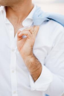 Мужчина в белой рубашке с обручальным кольцом держит куртку, перекинутую через плечо крупным планом