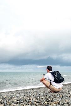 흰색 티셔츠와 베이지색 반바지를 입은 남자가 검은 배낭 관광객이 바다 전화로 사진과 비디오를 찍고 있습니다. 여행 블로그 개념