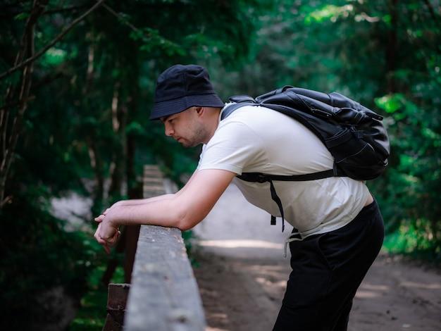 白いtシャツを着てバックパックを背負った男が橋の上に立って川を見ています