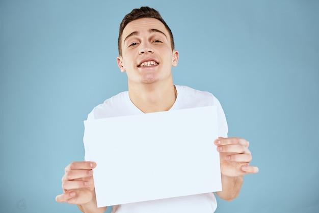 흰색 티셔츠에 남자가 그의 손에 종이 감정 자른 파란색 배경의보기를 보유하고 있습니다.