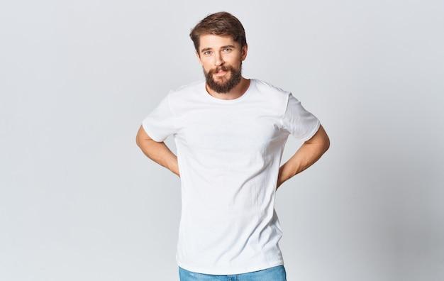 白いtシャツを着た男性が、ジーンズを手でトリミングして軽いジェスチャーをしています。