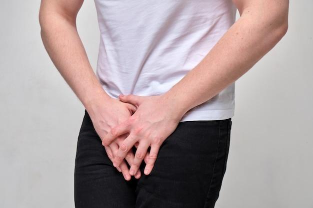 Мужчина в белой футболке страдает от паховой боли. проблема с урологией.