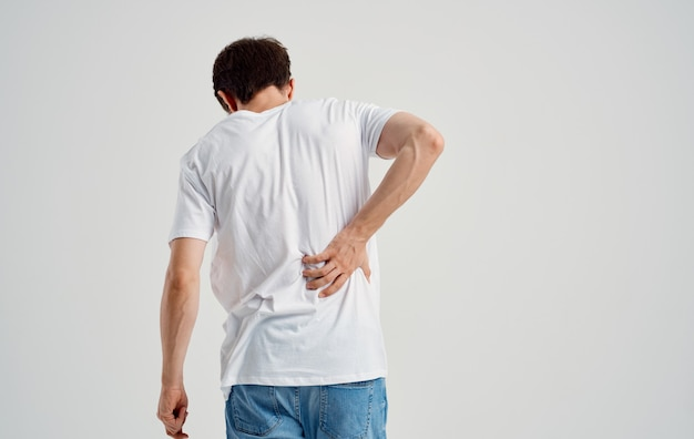 Мужчина в белой футболке трогает спину рукой боль в позвоночнике