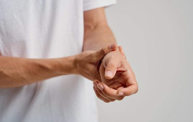흰색 티셔츠를 입은 남자가 밝은 배경에 손목을 만진다.