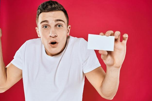 彼の手に名刺を持った白いtシャツの男感情赤い背景