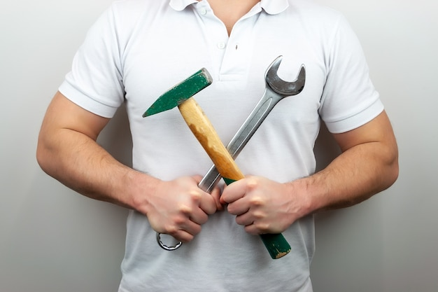 Мужчина в белой футболке с молотком и гаечным ключом