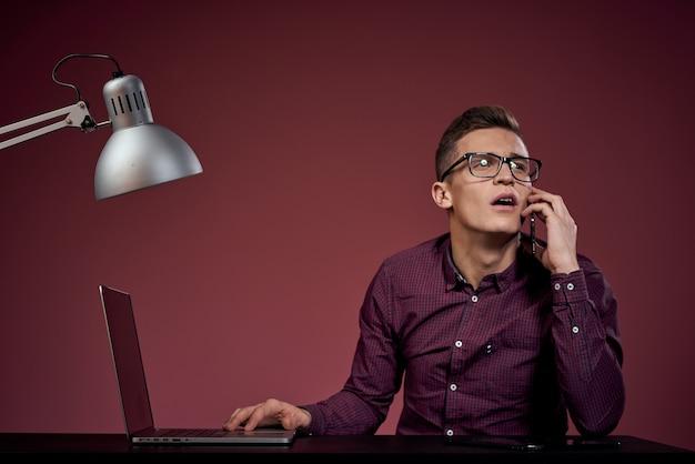 Человек в белой футболке с ноутбуком и электронным планшетом работает за столом