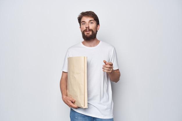 밝은 배경에 손에 종이 가방이 있는 흰색 티셔츠를 입은 남자