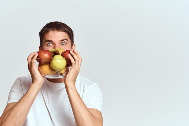 健康的な野菜と果物を手にした白いtシャツの男